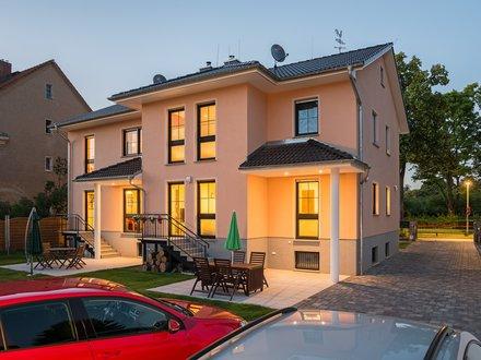 Mehrfamilienhäuser | Doppelhaus, Rückseite mit zwei Terrassen am Abend